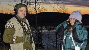 Jan ja Minna seisovat aamuauringon noustessa järvi taustallaan.