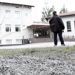 En människa står på en skolgård. Bilden har svaga färger.