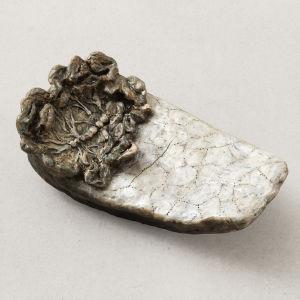 vitt keramikföremål med växtliknande ådrade formationer på vänstra ovansidan