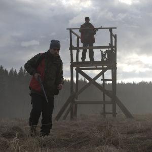 Joonas Saartamo med gevär i handen går mot kameran medan Peter Franzén håller utkik från ett jakttorn.
