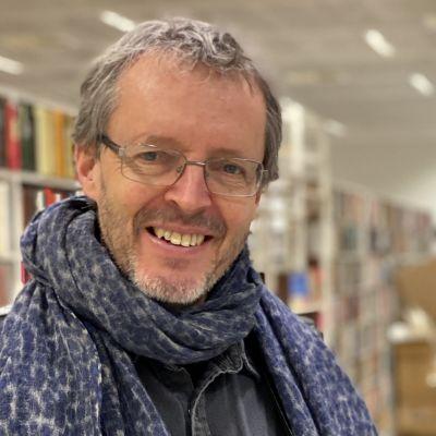 En leende man med glasögon framför rader av bokhyllor.