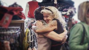 Vaalea, pitkähiuksinen nainen halaa tiukasti ja iloisesti tummempaa naista vaateliikkeessä.