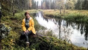 Nainen istuu joen rannalla.