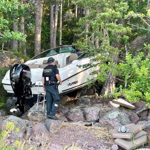 Båten har kört upp på land, den ligger på land vid en stenig strand vid skogsbrynet. En arbetare från Gränsbevakningsväsendet går mot båten.