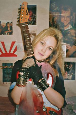Nuori nainen ja kitara. Taustalla artistien kuvia.