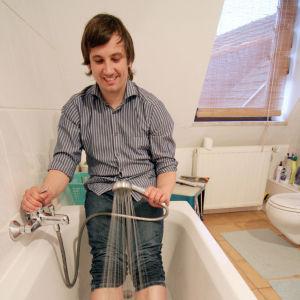 Man som iklädd jeans duschar fötterna i badkar.
