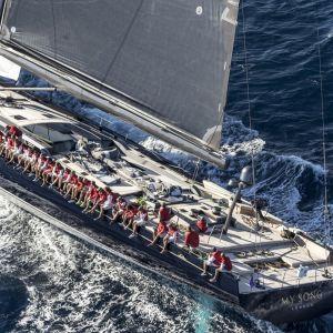 En stor segelbåt som åker i vattnet med ett 20-tal människor som sitter längs med relingen.