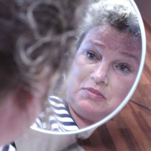 Nainen katsoo kasvojaan totisena peilistä.