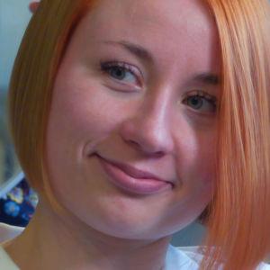Nuori, polkkatukkainen nainen katsoo hymyillen takanaan näkyvää peiliä.