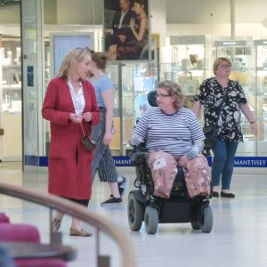 Stylisti Outi Broux kävelee kauppakeskuksessa pyörätuolilla kulkevan naisen rinnalla.