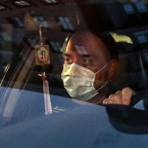 Mies istuu autossa maski kasvoillaan