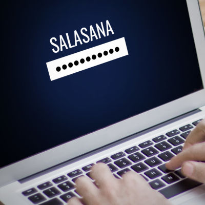 Kädet kirjoittavat kannettavalla tietokoneella. Ruudussa teksti salasana, sen alla palkki, jossa mustia palloja salasanaa kuvaamassa.