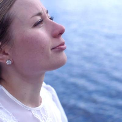 Nutturapäinen nuori nainen katsoo oikealle, taustalla järvi tai meri.
