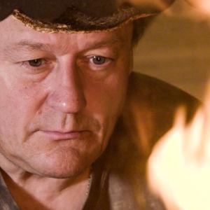 Totinen mies tuijottaa tuleen lierihattu päässä.