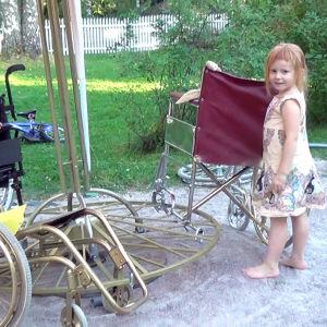 Kaksi pientä lasta, toinen rattaissa ja toinen seisomassa pihamaalla rakenteilla olevan taideteoksen vierellä.