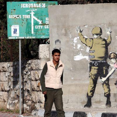 Mies kävelee ohi seinän, johon on maalattu sotilas ja häntä tarkastava tyttö.