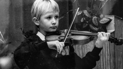 En svartvit bild Jakob som barn när han spelar violin.