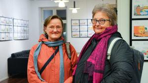 Två äldre kvinnor klädda i ytterjackor står inomhus och tittar in i kameran.
