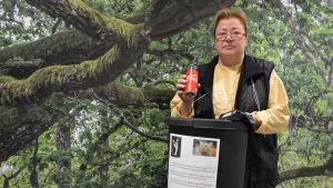 En medelålders kvinna håller upp en läskedrycksburk ovanför en papperskorg. På papperskorgen finns ett papper med kattbilder och text. Bakom kvinnan synns en vägg täckt av en tapet som liknar skog.