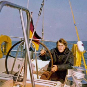 En man sitter i aktern på en segelbåt och håller i ratten.