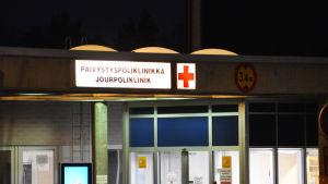 Bild på en byggnad som är upplyst i det omgivande mörkret. På en skylt står det jourpoliklinik.