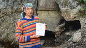En medelålders man i randig tröja och duk om huvudet står framför en låg grottöppning. Han håller i en bok.