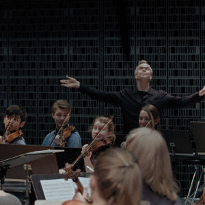 I-Han Fu dirigerar och Hannu Lintu slår ut med armarna bakom orkestern.