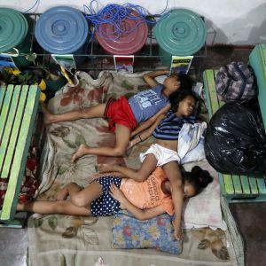 Kolme lasta nukkuu koulun lattialla patjoilla evakossa hirmumyrskyn takia Filippiineillä.