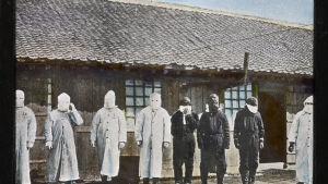 ett gammalt foto av läkare som virat bandage kring sina huvuden för att skydda sig mot lungpest