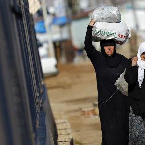 Syriska kvinnor bär på mat vid den Turkiska gränsen.