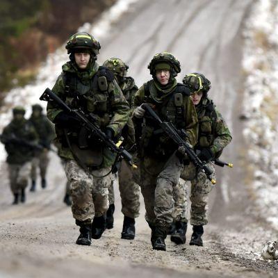 Beväringar i kamouflagekläder, hjälmar och med gevär går på en väg.
