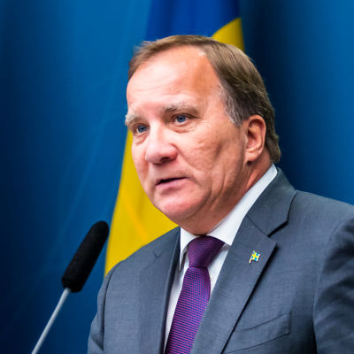Stefan Löfven framför Sveriges och EU:s flaggor.