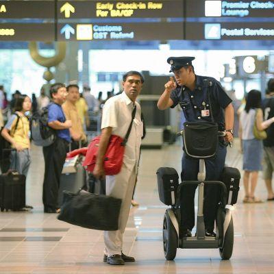 Singaporelainen poliisi opastaa matkustajaa Changin kansainvälisellä lentoasemalla.