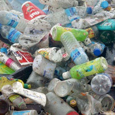 Tomma, smutsiga plastflaskor i en hög.