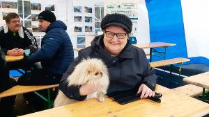 En dam sitter vid ett bord inne i ett tält. Under armen har hon en liten lurvig hund.
