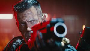 Robotmannen Cable (Josh Brolin) siktar med ett stort vapen i närbild.