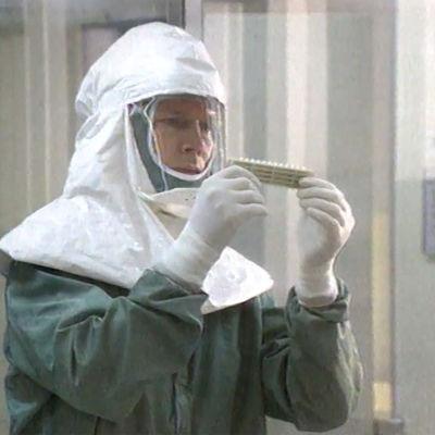Mies suojapuvussa laboratoriossa.