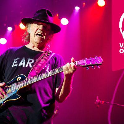 Neil Young har hatt på huvudet och han spelar elgitarr.