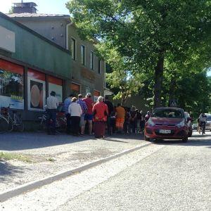 Folk köar utanför en tidigar mataffär där en förening delar ut mathjälp i Karis. Sommar. Bilar och cyklar syns också.
