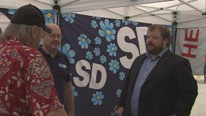 Richard Carrlsson talar med två män i Sverigedemokraternas valtält.