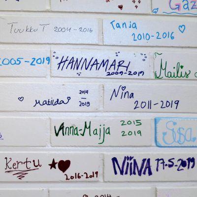 Entisten koululaisten nimimerkkejä lopetettavan koulun seinällä