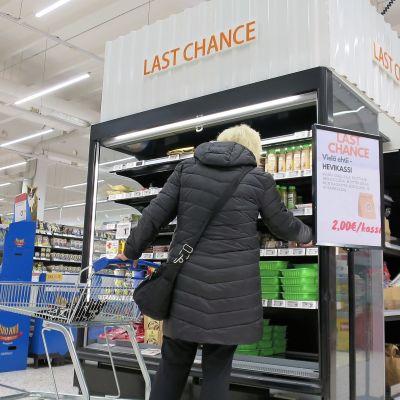 Nainen tutki hyllyä jossa lukee Last Chance