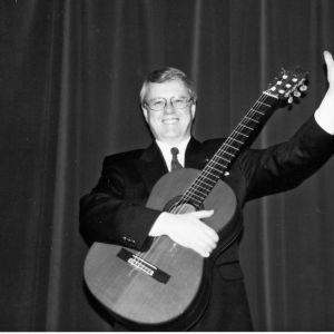 Bosse Österberg ler mot kameran och håller i en gitarr.