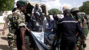 Säkerhetsstyrkor bär bort en av kropparna efter ett av bombdåden i Maroua i Kamerun den 22 juli 2015.