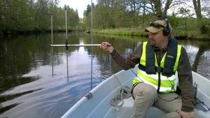 En man i en roddbåt med en antenn i sin hand och hörlurar på öronen. Han heter Juha-Pekka Vähä.