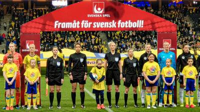 """Lina står uppställd på rad på fotbollsplanen i en spelarena med juniorfotbollsspelare och de andra domarna. En stor röd skärm med texten """"Framåt för svensk fotboll"""" står bakom dem."""
