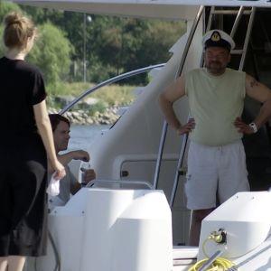 4 personer står ombord en båt.