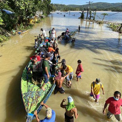 Ihmisiä ja vene tulvavedessä