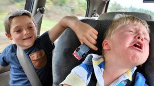 Kaksi lasta autonpenkillä, toinen itkee.