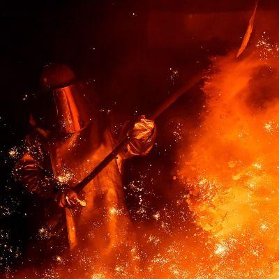 Dramatisk bild av skyddsklädd stålarbetare mitt i de gula flammorna på tyskt stålverk